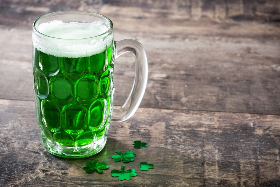 Traditional cold green beer on wooden table for Saint Patrick's Day. Copyspace.